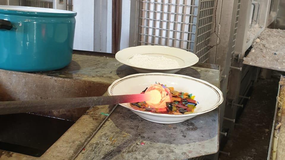 Potom se sklovina ještě obalí v předem připravených barevných střepech  (tzv. plaucny),  čímž se docílí požadované barevnosti. Foto: archiv Českého centra New York