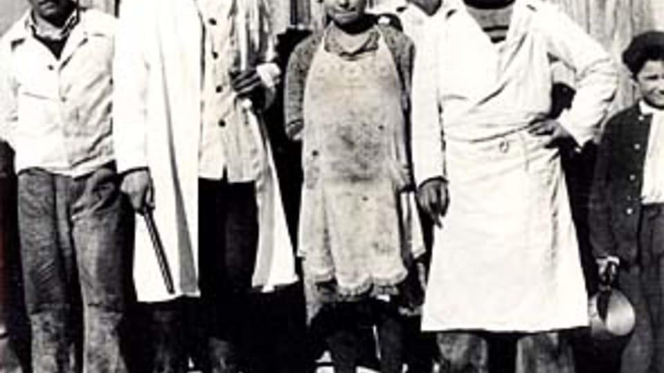 Vězni a dozorci v Letech,  za povšimnutí stojí pendrek v ruce druhého muže zleva; zdroj: fotografie z MRK  (originál uložen v NAP)